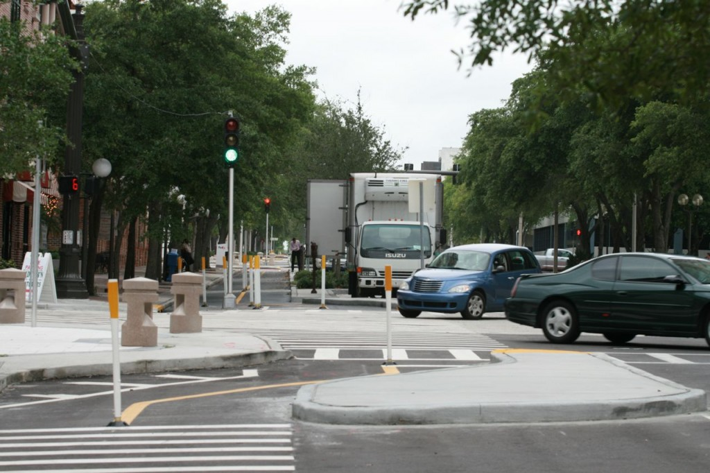 The green light is for the cycletrack, the street is one-way, but cars on the street can still turn right across the cyclists' path. The box truck obscures the view of the cycletrack for right-turning drivers. It also obscures cyclists' view of the road.